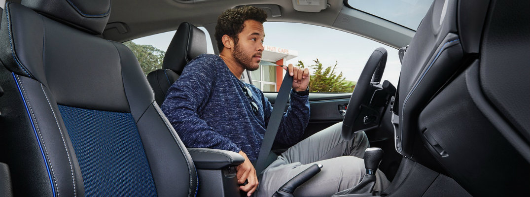 Man buckling up his seat belt inside 2018 Toyota Corolla