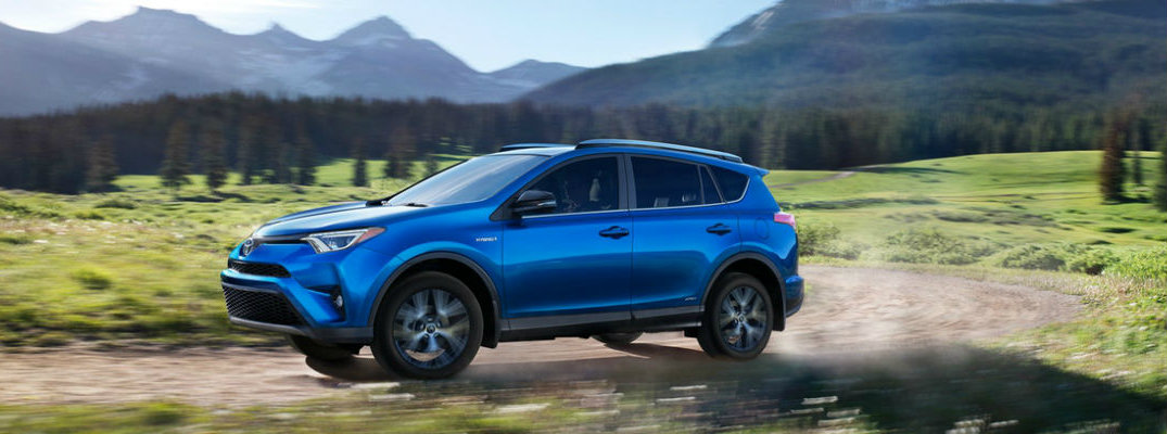 Blue 2018 Toyota RAV4 driving on mountain road