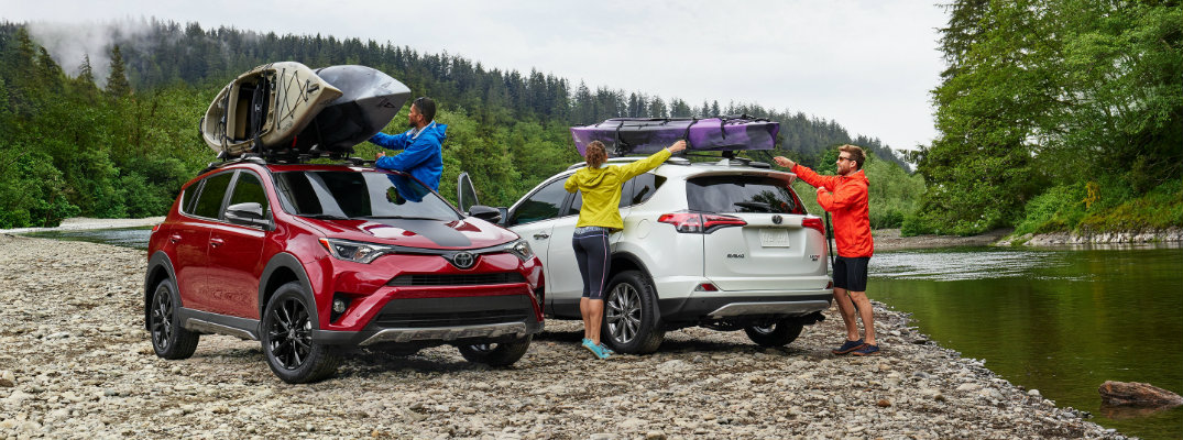 Red and white Toyota RAV4 parked on riverfront ground