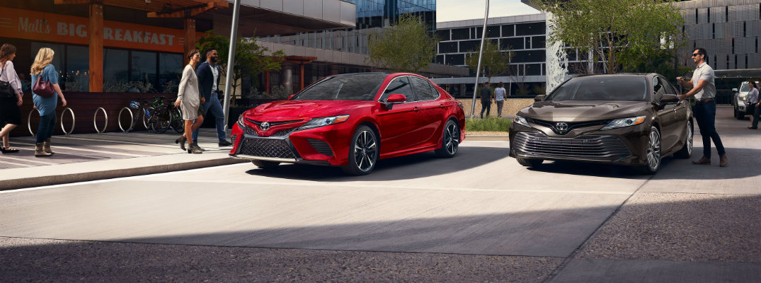 Two 2019 Toyota Camry models parked in front of modern building