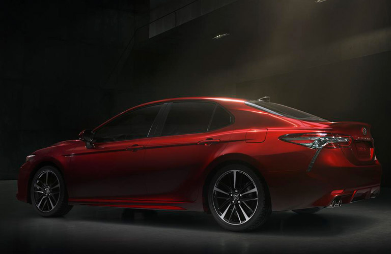 Profile view of red 2019 Toyota Camry driving on dark road