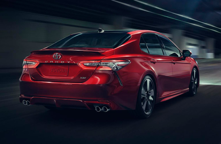 Rear shot of red 2019 Toyota Camry driving on dark road