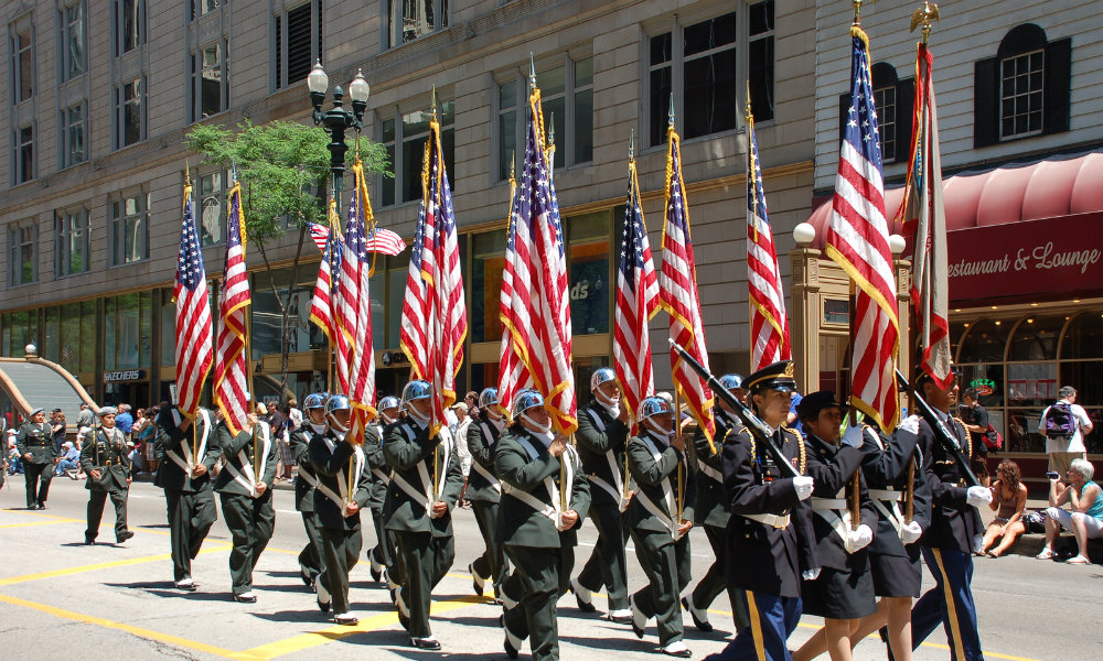 Military servicemen and women holding flags and marching during parade