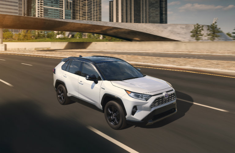 White 2019 Toyota RAV4 driving on city road