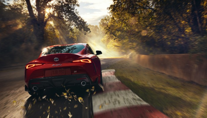 2020 Toyota Supra driving on tree-lined road