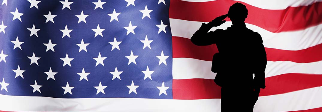 Silhouette of soldier saluting in front of American flag
