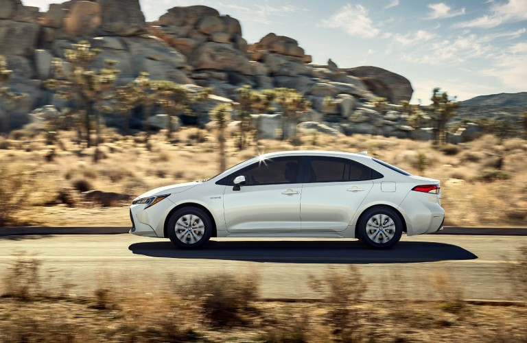 Profile view of white 2020 Toyota Corolla driving on desert road