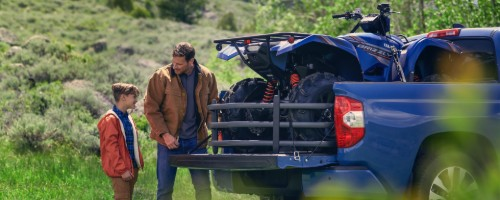 Father and son loading ATV in rear cargo area of 2020 Toyota Tundra