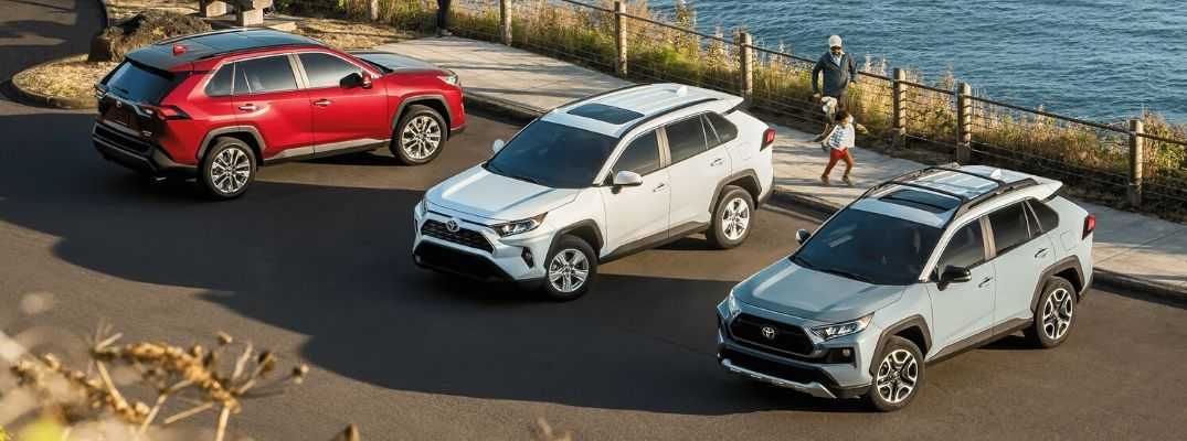 Exterior view of three 2020 Toyota RAV4 models parked in a parking lot