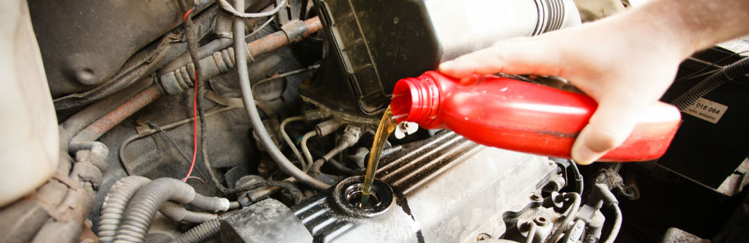 person pouring oil in an engine