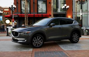 left side view of dark gray mazda cx-5 parked on city street