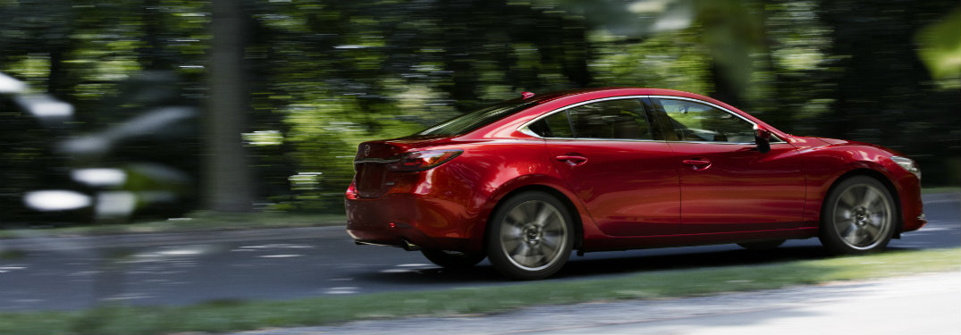 right side view of red mazda6 driving by trees