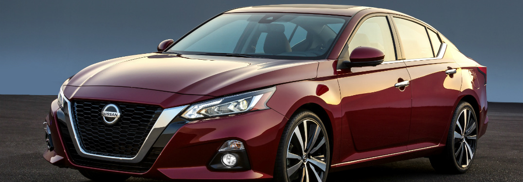 red 2019 nissan altima against black and blue background