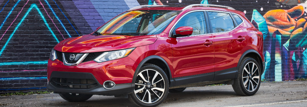 front and side view of red 2018 nissan rogue sport in front of wall mural