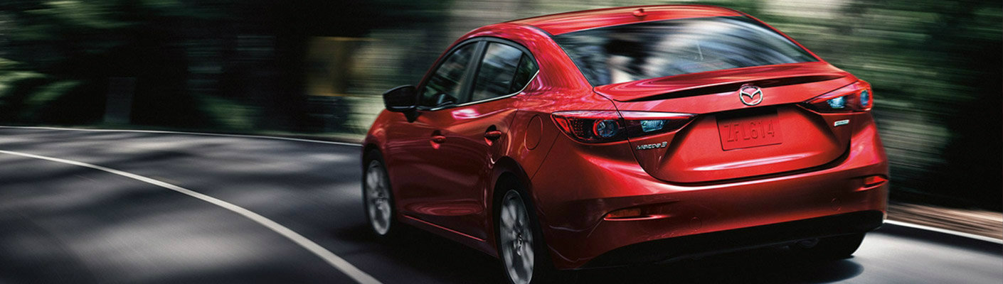 View of red 2019 Mazda3 driving down a road away from the camera