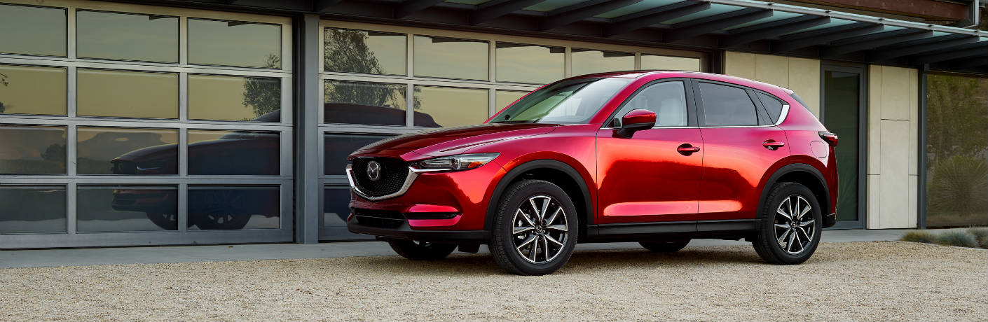 Exterior view of a red 2018 Mazda CX-5 parked outside a building with large glass windows