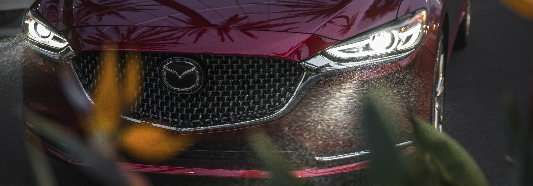 front end of dark red mazda6, headlights on