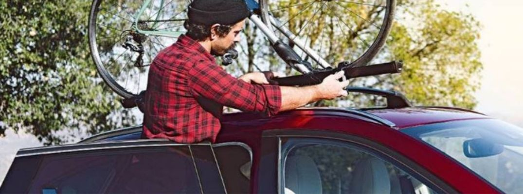 Image of a man placing a Mazda roof rack accessory on a red Mazda vehicle