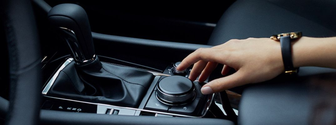 Interior view of a Mazda vehicle showing a driver using the Commander Control