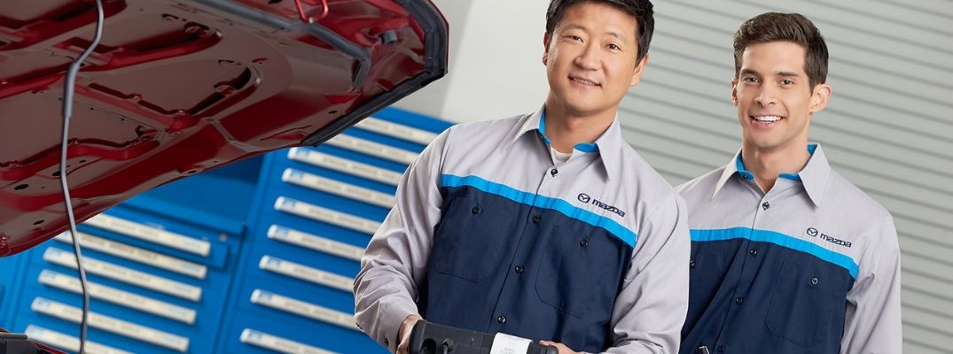 Image of two Mazda service technicians smiling for the camera while working on a Mazda vehicle