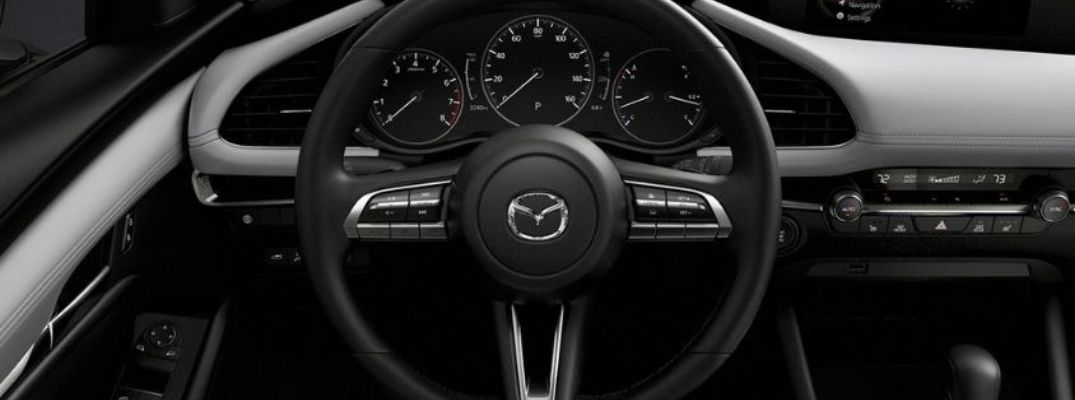 Closeup view of the steering wheel inside a Mazda vehicle