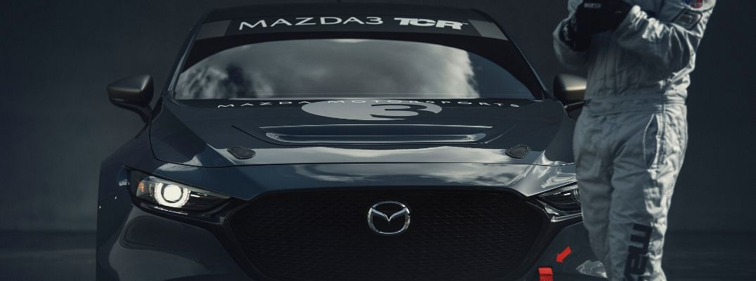 Closeup view of the front of the gray Mazda3 TCR with the driver standing nearby