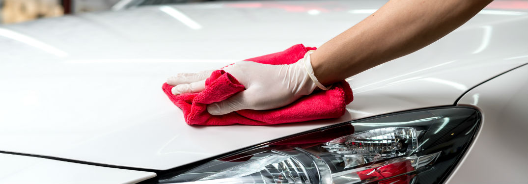 hand with white glove using red rag to wax car