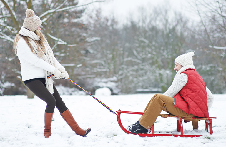 A woman pulling a man on a sled