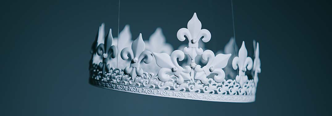 An elaborate white crown with a blue background