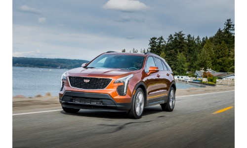 2019 Cadillac XT4 exterior shot with orange paint color driving on a seaside road next to a clear lake and forest