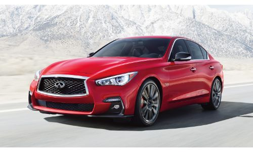 2020 Infiniti Q50 exterior shot with red paint color driving by white snowcapped mountains