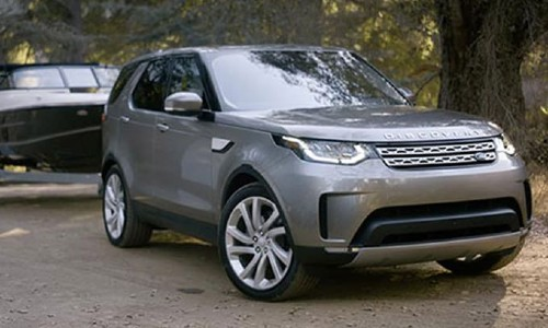 Land Rover Discovery exterior shot with gray paint color towing a boat through a forest