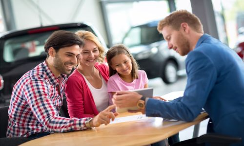 Family discussing a car with a salesman