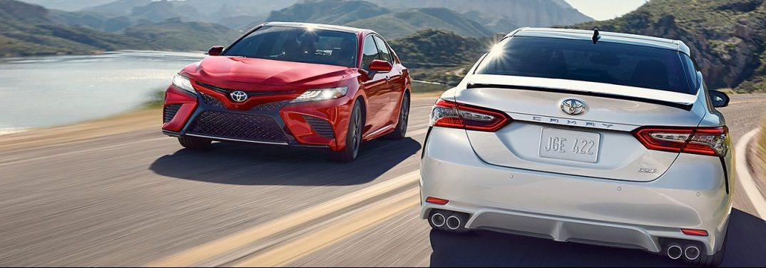 Two 2019 Toyota Camry vehicles drive past each other on a highway. A red model drives towards the camera while a silver drive away, revealing its rear.
