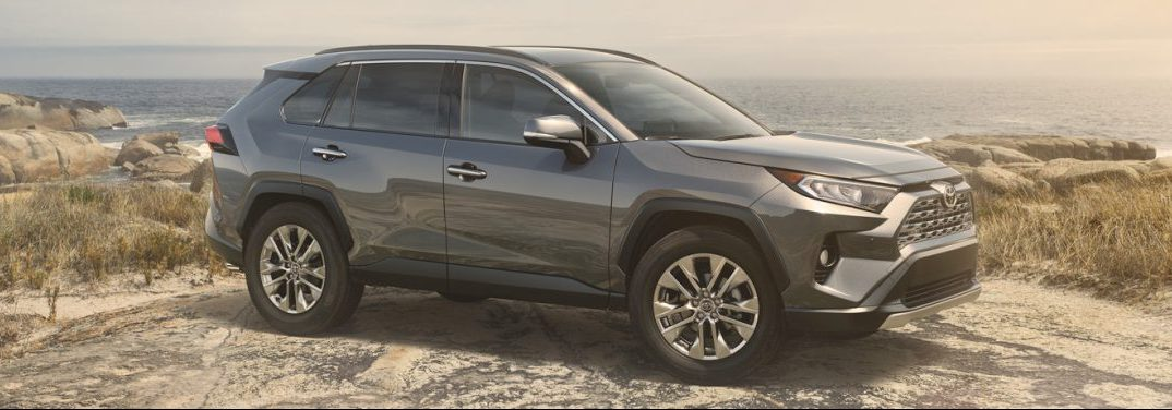 2019 Toyota RAV4 sits on a rugged landscape beside a body of water.