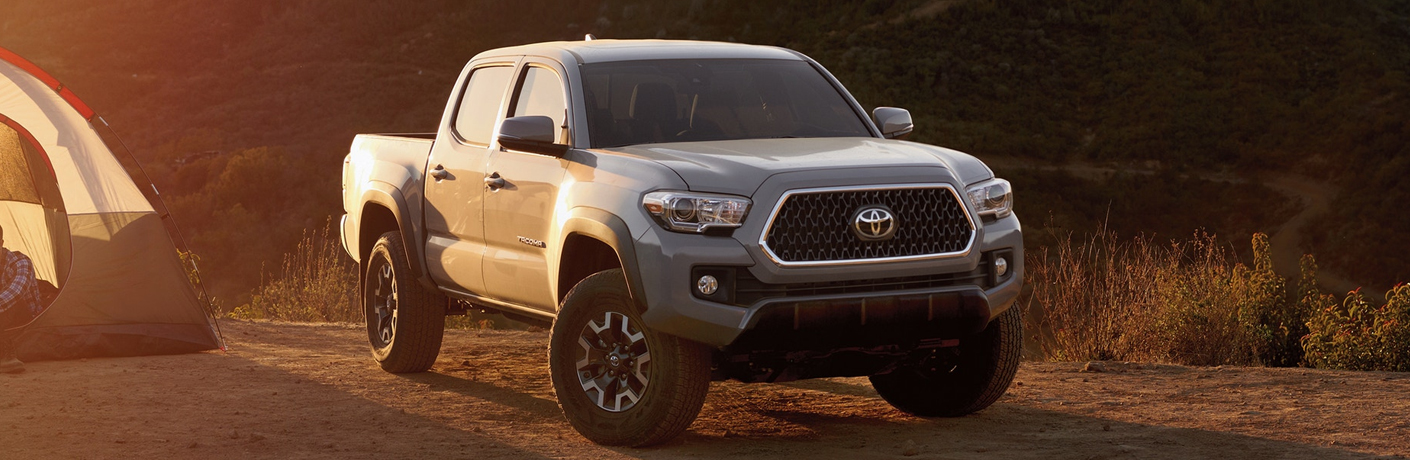 2019 Toyota Tacoma parked in a desert beside a tent.