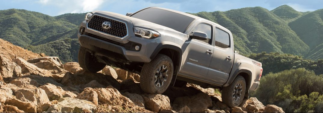 2019 Toyota Tacoma atop a rocky peak in a mountain range.