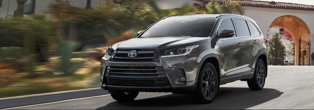 2019 Toyota Highlander drives down a scenic highway after going through a small arch.