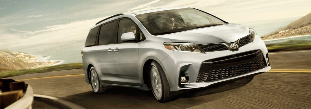 A 2019 Toyota Sienna rounds a highway curve in a striking yellow-tinted countryside.