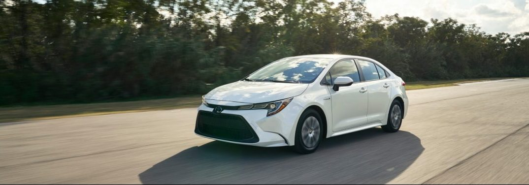 White 2020 Toyota Corolla cruises down an empty highway. Exterior front/side angled view.