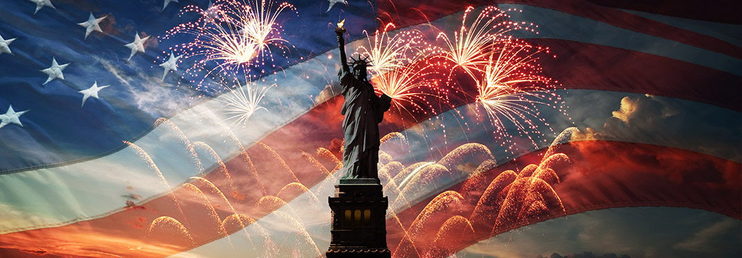 The Statue of Liberty against a background with the American flag and fireworks