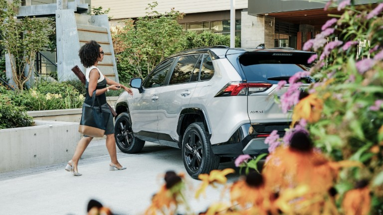 A woman talking out to the 2019 Toyota RAV4 Hybrid outside of her home