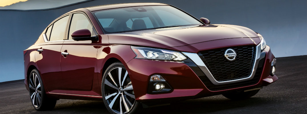 2019 Nissan Altima dark red exterior shot parked on dirt in the wilderness as the sun sets