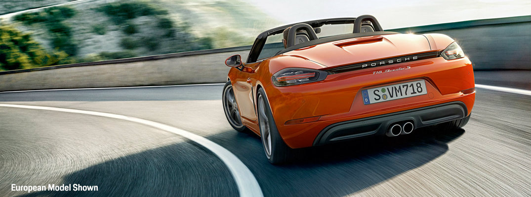 Rear view of orange 2018 Porsche 718 Boxster driving on winding road
