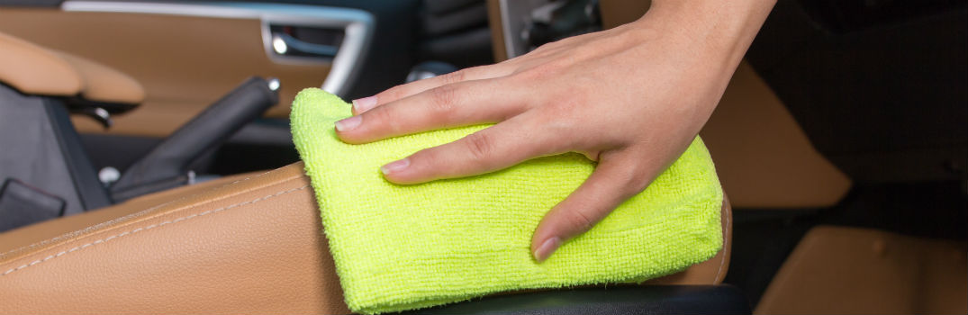 person wiping down dashboard with cloth