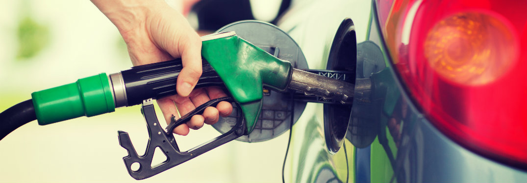 persons-hand-holding-gas-pump-filling-up-car