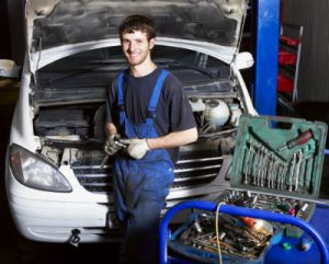 mechanic posing in front of a vehicle