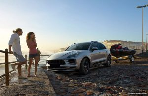 2020 Porsche Macan on a beach with two people standing next to it