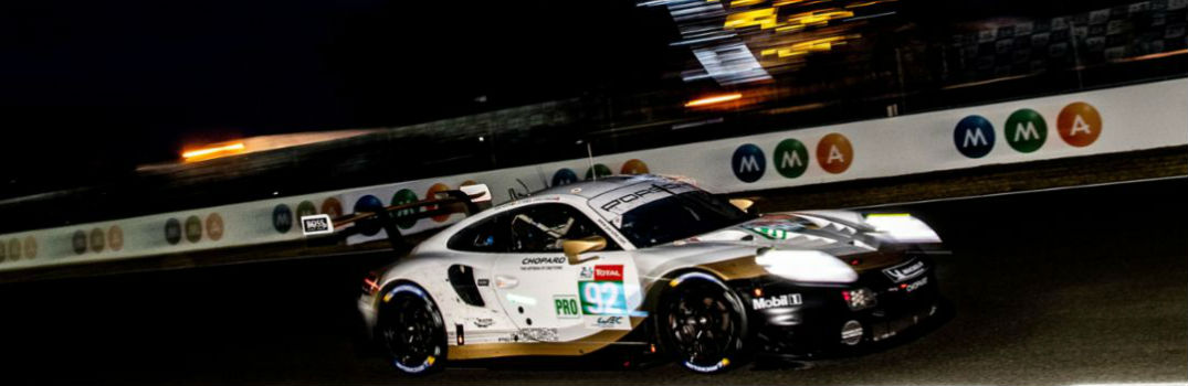 Porsche race car driving on a race track at night