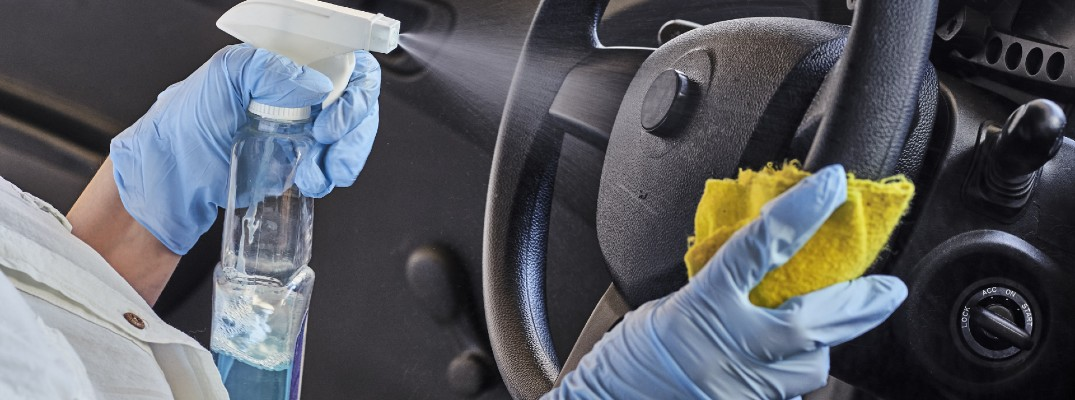 A stock photo of a person cleaning the inside of a car.